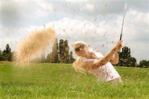 Female golfer tossing up dirt and dust after hitting her ball out of a sand trap.